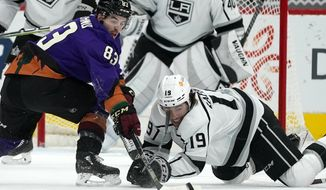 Arizona Coyotes right wing Conor Garland (83) battles with Los Angeles Kings right wing Alex Iafallo (19) for the puck during the second period of an NHL hockey game Saturday, Feb. 20, 2021, in Glendale, Ariz. (AP Photo/Ross D. Franklin)