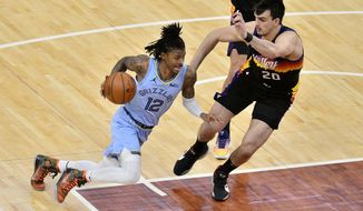 Memphis Grizzlies guard Ja Morant (12) drives against Phoenix Suns forward Dario Saric (20) in the second half of an NBA basketball game Saturday, Feb. 20, 2021, in Memphis, Tenn. (AP Photo/Brandon Dill)