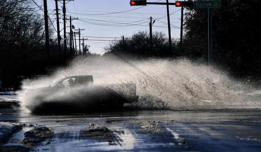 A pickup sends a wake of snow melt high into the air as the driver plows through a large puddle at Barrow and South 11th streets intersection in Abilene, Texas, Friday, Feb. 19, 2021. Temperatures climbed above freezing for the first time since Sunday's record 14.8-inch snowfall. (Ronald W. Erdrich, The Abilene Reporter-News via AP)