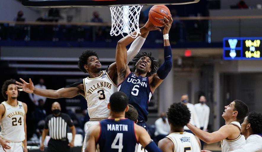 Connecticut's Isaiah Whaley (5) and Villanova's Brandon Slater (3) leap for a rebound during the second half of an NCAA college basketball game, Saturday, Feb. 20, 2021, in Villanova, Pa. (AP Photo/Matt Slocum)