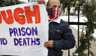 Ramiah Whiteside of Milwaukee holds a sign during a protest outside of the Wisconsin governor's mansion in Maple Bluff, Wis., on Nov. 24, 2020. Event organizers sought to draw attention to the thousands of inmates and staff who have contracted COVID-19 in state prisons and called for Gov. Tony Evers to slow the spread of the disease by reducing overcrowding. Whiteside is prison outreach director for Milwaukee-based Ex-incarcerated People Organizing, which is part of Wisdom, a statewide faith-based prison advocacy group. (Coburn Dukehart/Wisconsin Watch via AP)