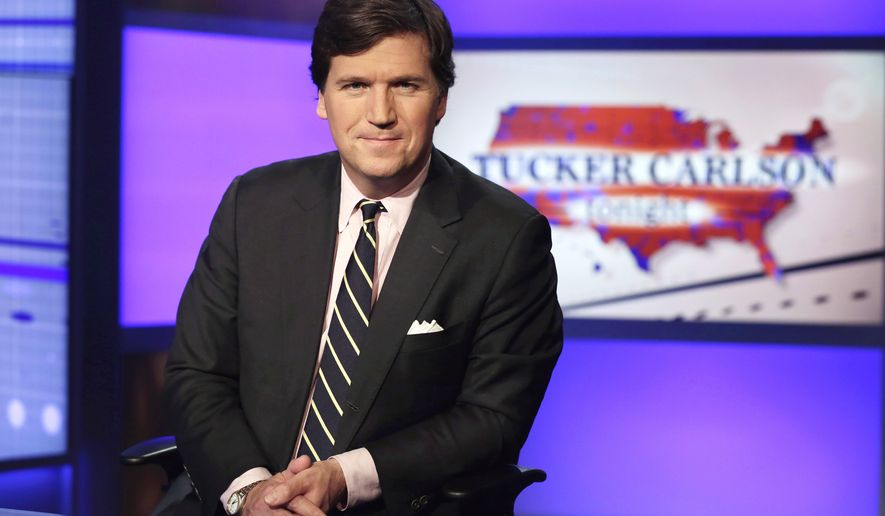 """FILE - Tucker Carlson, host of """"Tucker Carlson Tonight,"""" poses for photos in a Fox News Channel studio on March 2, 2017, in New York. Media critic Brian Stelter is updating his book """"Hoax: Donald Trump, Fox News and the Dangerous Distortion of Truth"""" in preparation for the paperback edition. The changes reflect the end of Trump's presidency and the false claims of voter fraud and the rise of Carlson to become Fox's most prominent personality. Announced on Sunday, Feb, 21, 2021, the revised edition will be released in June. (AP Photo/Richard Drew, File)"""