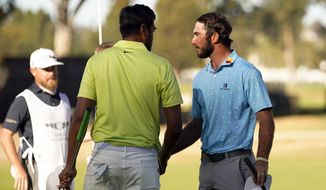 Max Homa, right, shakes hands with Tony Finau, center, on the 14th green after defeating him in a two-hole playoff during the final round of the Genesis Invitational golf tournament at Riviera Country Club, Sunday, Feb. 21, 2021, in the Pacific Palisades area of Los Angeles. (AP Photo/Ryan Kang)