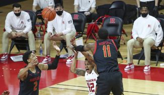 The Rutgers bench watches as Maryland guard Darryl Morsell (11) swats away a shot by Rutgers guard Jacob Young (42) during the second half of an NCAA college basketball game in Piscataway, N.J., Sunday, Feb. 21, 2021. (Andrew Mills/NJ Advance Media via AP)