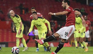 Manchester United's Bruno Fernandes scores his side's third goal from the penalty spot during an English Premier League soccer match between Manchester United and Newcastle at the Old Trafford stadium in Manchester, England, Sunday Feb. 21, 2021. (Stu Forster/Pool via AP)