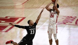 Houston guard Quentin Grimes (24) shoots a 3-point basket as Cincinnati guard Mika Adams-Woods defends during the second half of an NCAA college basketball game, Sunday, Feb. 21, 2021, in Houston. (AP Photo/Eric Christian Smith)