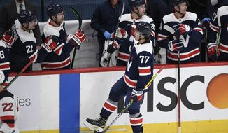 Washington Capitals right wing T.J. Oshie (77) celebrates his goal with the bench during the second period of an NHL hockey game against the New Jersey Devils, Sunday, Feb. 21, 2021, in Washington. (AP Photo/Nick Wass)
