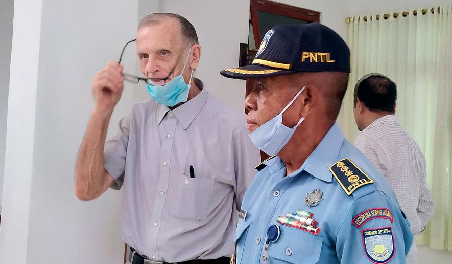 A police officer escorts Richard Daschbach, center, a former missionary from Pennsylvania, U.S. upon his arrival for a trial at a courthouse in Oecusse, East Timor, Monday, Feb. 22, 2021. The defrocked American priest was set to go on trial Monday to face allegations he sexually abused young girls at a children's shelter he ran in a remote enclave in East Timor — one of the most Catholic places on Earth. (AP Photo)
