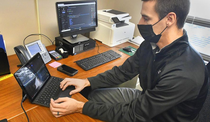 Matt Frahm, youth sports and teen supervisor for the Town of Normal, Ill., logs in to a gaming site as part of his efforts to build on a local esports gaming league at the Normal Activity Center, Tuesday, Feb. 10, 2021. The computer in the background displays a Discord communications program used by gamers. (David Proeber/The Pantagraph via AP)