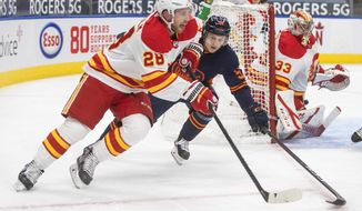Edmonton Oilers' Kailer Yamamoto (56) chases Calgary Flames' Elias Lindholm (28) during the second period of an NHL hockey game Saturday, Feb. 20, 2021, in Edmonton, Alberta. (Jason Franson/The Canadian Press via AP)
