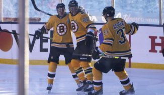 Boston Bruins right wing David Pastrnak, center, celebrates with teammates Brad Marchand, left and Patrice Bergeron after scoring against the Philadelphia Flyers in the first period of an NHL hockey game in Stateline, Nev., Sunday, Feb. 21, 2021. (AP Photo/Rich Pedroncelli))