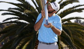 Max Homa kisses his trophy on the practice green after winning the Genesis Invitational golf tournament at Riviera Country Club, Sunday, Feb. 21, 2021, in the Pacific Palisades area of Los Angeles. (AP Photo/Ryan Kang)