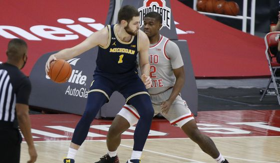 Michigan's Hunter Dickinson, left, posts up against Ohio State's E.J. Liddell during the first half of an NCAA college basketball game Sunday, Feb. 21, 2021, in Columbus, Ohio. (AP Photo/Jay LaPrete) **FILE**