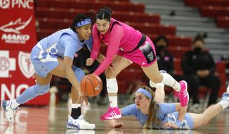 N.C. State's Raina Perez (2) keeps the ball from North Carolina's Kennedy Todd-Williams (3) after stealing the ball during the first half of a college basketball game in the annual Play4Kay game at Reynolds Coliseum in Raleigh, N.C., Sunday, Feb. 21, 2021. (Ethan Hyman/The News & Observer via AP)