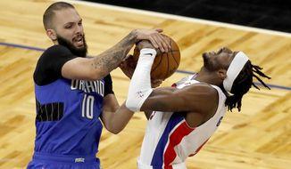 Orlando Magic guard Evan Fournier (10) battles Detroit Pistons forward Jerami Grant (9) for the ball in the first half during an NBA basketball game, Sunday, Feb. 21, 2021, in Orlando, Fla. (AP Photo/Joe Skipper)