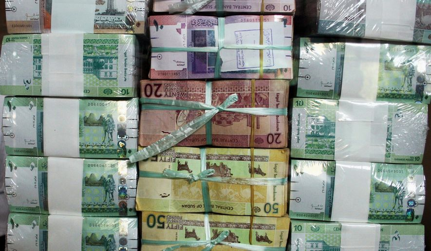 FILE - In this July 24, 2011, file photo, Sudan's new currency sits behind a window at the central bank in Khartoum, Sudan. The country took the unprecedented but expected step of floating its currency Sunday, Feb. 21, 2021, meeting a major demand by international financial insinuations to help transitional authorities overhaul the battered economy. (AP Photo/Abd Raouf, File)