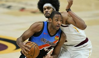 Oklahoma City Thunder's Al Horford (42) drives against Cleveland Cavaliers' Jarrett Allen in the second half of an NBA basketball game, Sunday, Feb. 21, 2021, in Cleveland. (AP Photo/Tony Dejak)