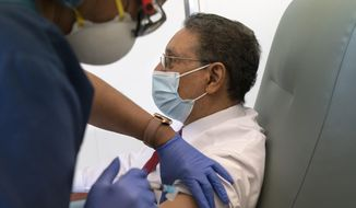 In this Wednesday, Feb. 10, 2021, photo Wallace Charles Smith, 72, who is a pastor at Shiloh Baptist Church, receives his first COVID-19 vaccination by nurse Michelle Martin, at United Medical Center in southeast Washington. (AP Photo/Jacquelyn Martin)