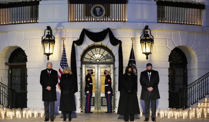 From left, President Joe Biden, first lady Jill Biden, Vice President Kamala Harris and her husband Doug Emhoff, bow their heads during a ceremony to honor the 500,000 Americans that died from COVID-19, at the White House, Monday, Feb. 22, 2021, in Washington. (AP Photo/Evan Vucci)