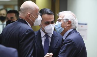 Greek Foreign Minister Nikos Dendias, left, greets Italy's Foreign Minister Luigi Di Maio, center, and European Union foreign policy chief Josep Borrell during a meeting of EU foreign ministers at the European Council building in Brussels, Monday, Feb 22, 2021. European Union foreign ministers on Monday will look at options for imposing fresh sanctions against Russia over the jailing of opposition leader Alexei Navalny as the 27-nation bloc considers the future of its troubled ties with the country. (Yves Herman, Pool via AP)