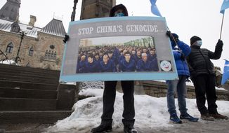 Protesters gather outside the Parliament buildings in Ottawa, Ontario, Monday, Feb. 22, 2021. Parliament is expected to vote on an opposition motion calling on Canada to recognize China's actions against ethnic Muslim Uighurs as genocide. (Adrian Wyld/The Canadian Press via AP)