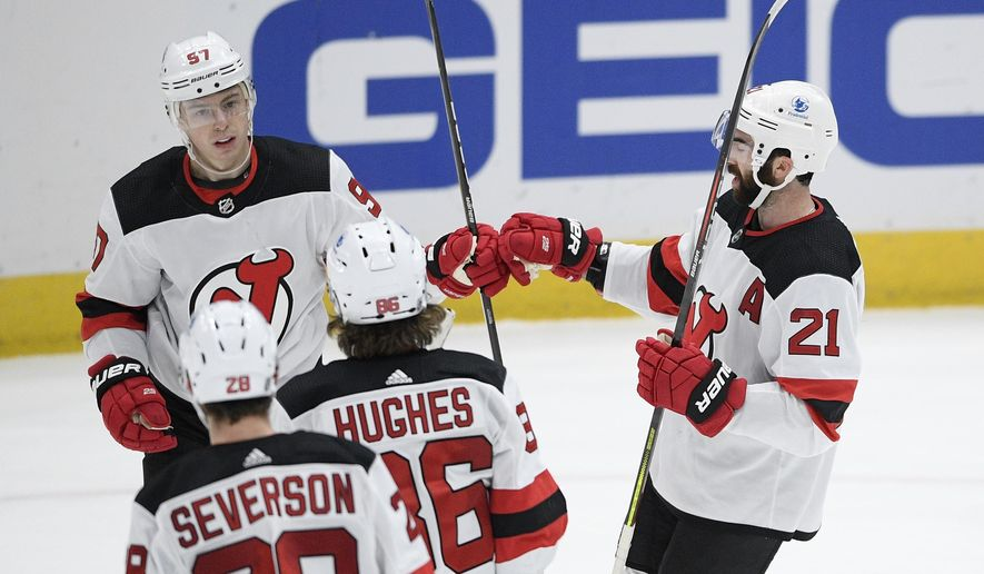 New Jersey Devils left wing Nikita Gusev (97) celebrates his goal with right wing Kyle Palmieri (21), center Jack Hughes (86) and defenseman Damon Severson (28) during the third period of an NHL hockey game against the Washington Capitals, Sunday, Feb. 21, 2021, in Washington. (AP Photo/Nick Wass)