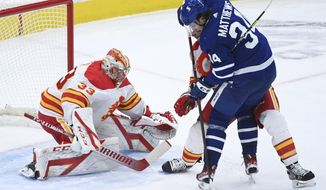 Toronto Maple Leafs centre Auston Matthews (34) gets tied up by Calgary Flames defenceman Mark Giordano (5) as Flames goaltender David Rittich (33) keeps a close eye on the loose puck during third period NHL hockey action in Toronto on Monday, Feb. 22, 2021. (Nathan Denette/The Canadian Press via AP)