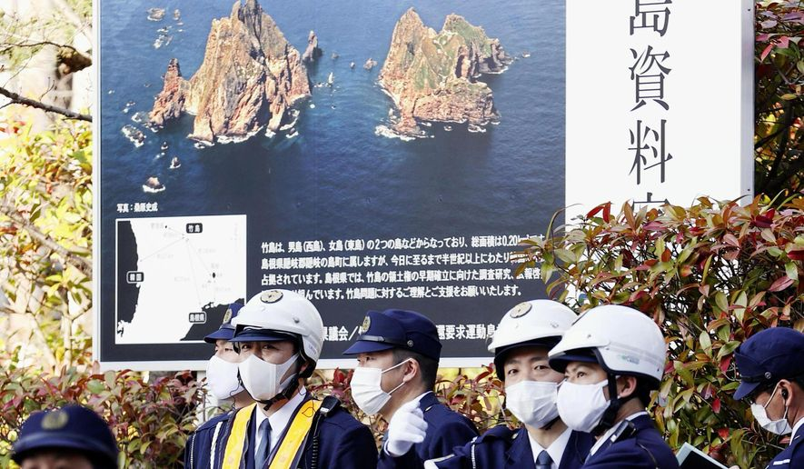 """Police officers stand guard near the venue of a ceremony to mark Shimane Prefecture-designated """"Takeshima Day"""" in Matsue, Shimane prefecture, western Japan, Monday, Feb. 22, 2021. Japan renewed its claim on a contested island in the Sea of Japan held by South Korea at an annual event Monday, escalating tensions between the neighbors were already strained over Seoul's compensation claim over Tokyo's World War II atrocities. The island is called """"Takeshima"""" in Japan and """"Dokdo"""" in South Korea. The poster in the background reads: """"Takeshima is Shimane's treasure, my territory."""" (Kyodo News via AP) ** FILE **"""