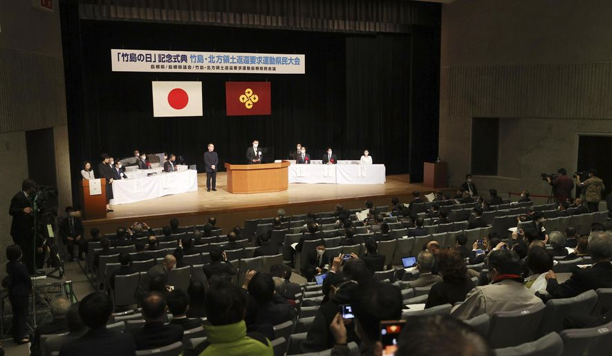 """Shimane Gov. Tatsuya Maruyama, center, delivers a speech during a ceremony to mark Shimane Prefecture-designated """"Takeshima Day"""" in Matsue, Shimane prefecture, western Japan, Monday, Feb. 22, 2021. Japan renewed its claim on a contested island in the Sea of Japan held by South Korea at the annual event Monday, escalating tensions between the neighbors were already strained over Seoul's compensation claim over Tokyo's World War II atrocities. The island is called """"Takeshima"""" in Japan and """"Dokdo"""" in South Korea. (Kyodo News via AP)"""
