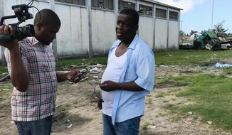 FILE - In this Monday March 25, 2019 file photo, Beira Mayor Daviz Simango, right, pauses from directing disaster relief operations in Beira, Mozambique. Simango, the leader of Mozambique's opposition MDM party and the mayor of the major port city of Beira, has died in a South Africa hospital, according to local media on Monday, Feb. 22, 2021. Party officials said Simango, 57, died of complications from COVID-19, diabetes and a stroke. (AP Photo/Cara Anna, file)