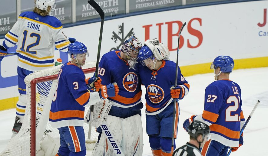 New York Islanders goaltender Semyon Varlamov (40) celebrates with Islanders center Jean-Gabriel Pageau (44) as defenseman Adam Pelech (3) and center Anders Lee (27) look on while Buffalo Sabres center Eric Staal (12) skates away after the New York Islanders defeated the Sabres 3-2 in an NHL hockey game, Monday, Feb. 22, 2021, in Uniondale, N.Y. (AP Photo/Kathy Willens)