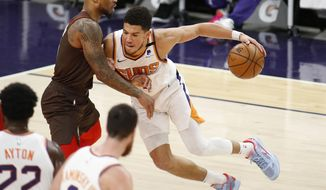 Phoenix Suns' Devin Booker muscles his way towards the basket against Portland Trail Blazers' Damien Lillard during the first half of an NBA basketball game Monday, Feb. 22, 2021, in Phoenix. (AP Photo/Darryl Webb)