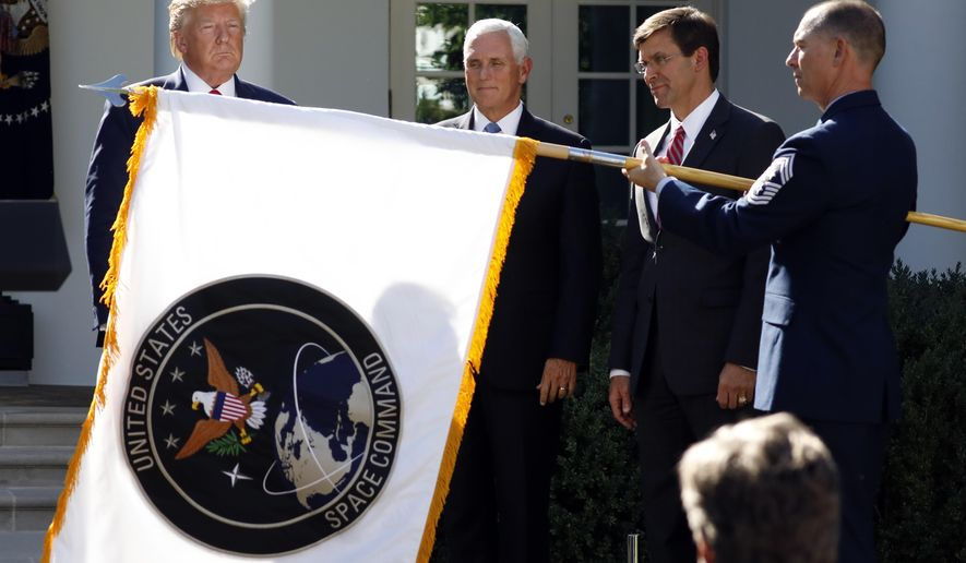 FILE - In this Aug. 29, 2019, file photo, President Donald Trump, left, watches with Vice President Mike Pence and Defense Secretary Mark Esper as the flag for U.S. space Command is unfurled as Trump announces the establishment of the U.S. Space Command in the Rose Garden of the White House in Washington. The Department of the Defense Inspector General on Friday, Feb. 19, 2021, has announced an investigation into the Trump administration's January decision to move the U.S. Space Command headquarters from Peterson Air Force Base in Colorado to the Redstone Arsenal adjacent to Huntsville, Ala. The announcement follows protests by Colorado's congressional delegation that the decision was politically motivated. (AP Photo/Carolyn Kaster, File)