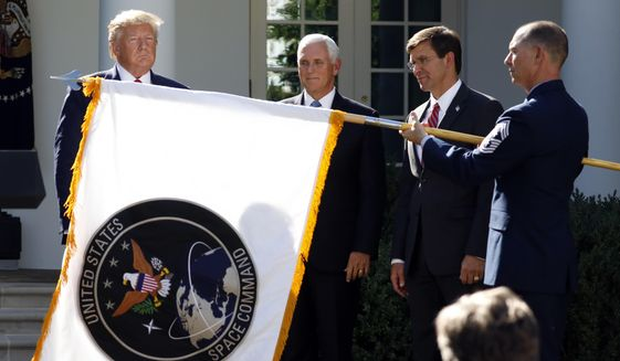 In this Aug. 29, 2019, photo, President Donald Trump, left, watches with Vice President Mike Pence and Defense Secretary Mark Esper as the flag for U.S. Space Command is unfurled as Trump announces the establishment of the U.S. Space Command in the Rose Garden of the White House in Washington. (AP Photo/Carolyn Kaster) **FILE**