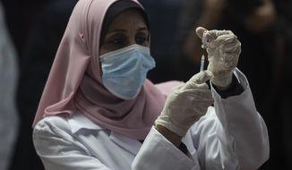 A Palestinian medic prepares a shot of the Russian-made Sputnik V coronavirus vaccine, in Gaza City, Monday, Feb. 22, 2021. (AP Photo/Khalil Hamra)