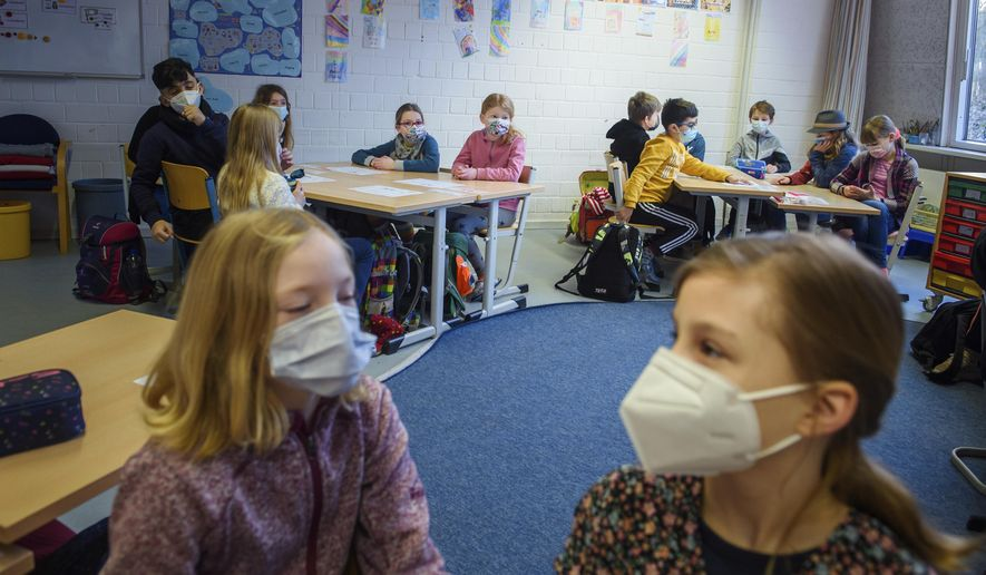 Pupils attend a lesson at the 'Russee' elementary school in Kiel, northern Germany, Monday, Feb. 22, 2021. Elementary schools and kindergartens in more than than half of Germany's 16 states reopened Monday after two months of closure due to the coronavirus pandemic. The move comes despite growing signs that the decline in case numbers in Germany is flattening out again and even rising in some areas. (Gregor Fischer/dpa via AP)