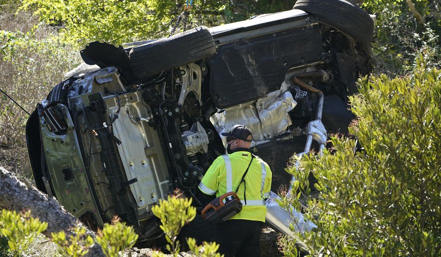 A vehicle rests on its side after a rollover accident involving golfer Tiger Woods Tuesday, Feb. 23, 2021, in the Rancho Palos Verdes section of Los Angeles. Woods suffered leg injuries in the one-car accident and was undergoing surgery, authorities and his manager said. (AP Photo/Marcio Jose Sanchez)