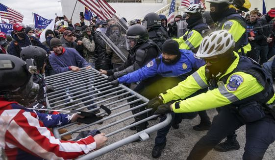 In this Jan. 6, 2021, photo, rioters try to break through a police barrier at the Capitol in Washington. (AP Photo/John Minchillo) **FILE**