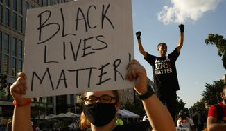 In this June 24, 2020, file photo, Antonio Mingo, of Washington, right, holds his fists in the air as demonstrators protest in front of a police line on a section of 16th Street that's been renamed Black Lives Matter Plaza in Washington, following the death of George Floyd, a black man who was in police custody in Minneapolis. A financial snapshot shared exclusively with The Associated Press shows the Black Lives Matter Global Network Foundation took in just over $90 million last year. (AP Photo/Jacquelyn Martin, File)