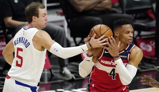 Washington Wizards guard Russell Westbrook, right, is stripped of the ball by Los Angeles Clippers guard Luke Kennard during the first half of an NBA basketball game Tuesday, Feb. 23, 2021, in Los Angeles. (AP Photo/Mark J. Terrill)