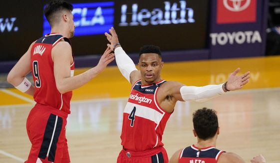 Washington Wizards guard Russell Westbrook, center, congratulates teammates forward Deni Avdija, left, and guard Raul Neto during a timeout in the second half of an NBA basketball game Monday, Feb. 22, 2021, in Los Angeles. The Wizards won 127-124 in overtime. (AP Photo/Mark J. Terrill) **FILE**