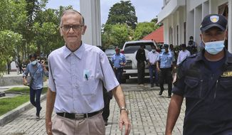 A police officer escorts Richard Daschbach, left, a former missionary from Pennsylvania, U.S. upon his arrival for a trial at a courthouse in Oecusse, East Timor, Tuesday, Feb. 23, 2021. The defrocked American priest went on trial Tuesday to face charges he sexually abused young girls at his shelter for orphans and children from impoverished families, marking the first clergy sex case to emerge in East Timor, the most Catholic place in the world outside the Vatican. (AP Photo/Raimundos Oki)