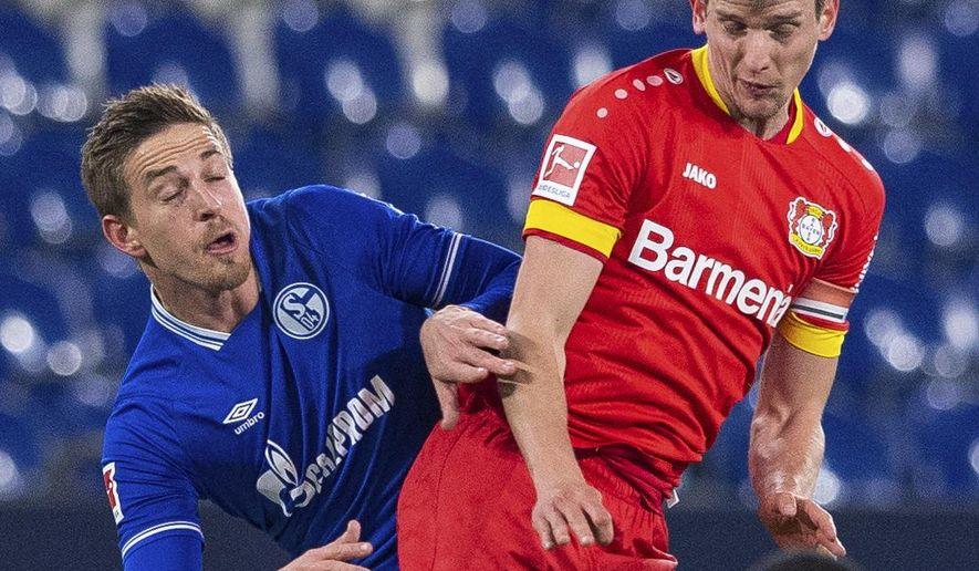 Leverkusen's Lars Bender, right, challenged by Schalke's Bastian Oczipka during their German Bundesliga soccer match at the Veltins Arena in Gelsenkirchen, Germany, Sunday Dec. 6, 2020.  (Guido Kirchner/pool via AP)