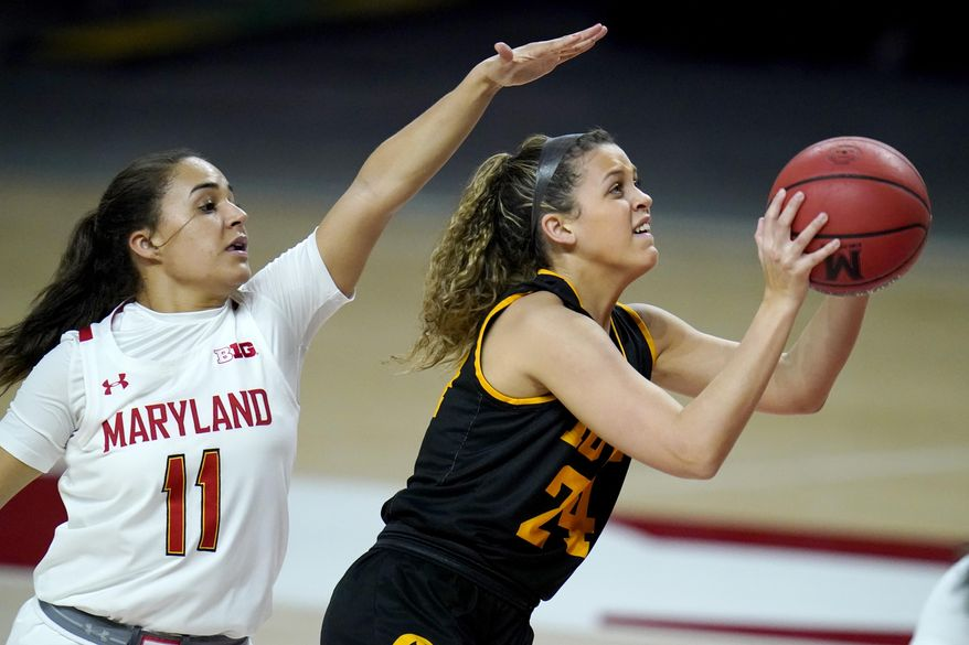 Iowa guard Gabbie Marshall, right, shoots a basket against Maryland guard Katie Benzan during the first half of an NCAA college basketball game, Tuesday, Feb. 23, 2021, in College Park, Md. (AP Photo/Julio Cortez)