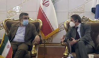 """FILE - In this Feb. 20, 2021, file photo, Director General of International Atomic Energy Agency, IAEA, Rafael Mariano Grossi, right, speaks with spokesman of Iran's atomic agency Behrouz Kamalvandi upon his arrival at Tehran's Imam Khomeini airport, Iran. Iran has said it plans to cease its implementation of the """"Additional Protocol,"""" a confidential agreement between Tehran and the IAEA reached as part of the landmark nuclear accord that grants the U.N. inspectors enhanced powers to visit nuclear facilities and watch Iran's program. (Atomic Energy Organization of Iran via AP, File)"""