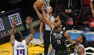 Sacramento Kings forward Marvin Bagley III tries to steal the ball from Brooklyn Nets guard Kyrie Irving (11) during the first half of an NBA basketball game, Tuesday, Feb. 23, 2021, in New York, as Sacramento Kings guards DaQuan Jeffries (19) and Buddy Hield (24) watch from the floor. (AP Photo/Kathy Willens)