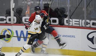 Pittsburgh Penguins center Zach Aston-Reese (12) checks Washington Capitals center Nicklas Backstrom (19) into the boards during the second period of an NHL hockey game, Tuesday, Feb. 23, 2021, in Washington. (AP Photo/Nick Wass)