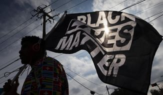 In this Dec. 12, 2020, file photo, MD Crawford carries a Black Lives Matter flag before a march in La Marque, Texas to protest the shooting of Joshua Feast, 22, by a La Marque police officer.  (Stuart Villanueva /The Galveston County Daily News via AP, File)  **FILE**