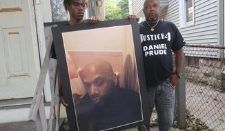"""FILE - In this Sept. 3, 2020, file photo, Joe Prude, brother of Daniel Prude, right, and his son Armin, stand with a picture of Daniel Prude in Rochester, N.Y. Daniel Prude, 41, suffocated after police in Rochester put a """"spit hood"""" over his head while he was being taken into custody. He died March 30, after he was taken off life support, seven days after the encounter with police. The independent investigator leading a probe of the city's handling of Prude's death says the ex-police chief is refusing to cooperate. (AP Photo/Ted Shaffre, File)"""