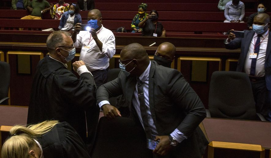 State prosecutor Advocate Billy Downer, left, greets members of the legal team representing former President Jacob Zuma, inside the High Court in Pietermaritzburg, South Africa, Tuesday, Feb. 23, 2021. A South African judge said he will file a criminal complaint against former South African president Jacob Zuma after he staged a dramatic walkout while attending a commission of inquiry looking into corruption during his tenure from 2009 to 2018. (AP Photo/Themba Hadebe)